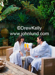 A couple celebrating their anniversary at a tropical resort spa. They are in their white bathrobes toasting with their mimosas in a lush green patio setting.